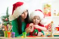 Mother and kid daughter in Santa hats making Royalty Free Stock Photo
