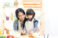 Mother and kid girl cooking and cutting vegetables
