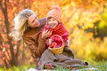 Mother and kid have pinic together in autumn park Royalty Free Stock Photo