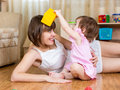 Mother and kid having fun pastime indoors girl Royalty Free Stock Image