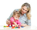 Mother and kid play with colorful puzzle toy Stock Photos