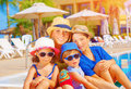 Mother with kids on beach resort relaxing sitting near poolside active summer holidays young tourists happy family concept Royalty Free Stock Photo