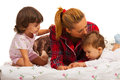 Mother with kids in bed her lying on and mom kissing little baby head Stock Photography