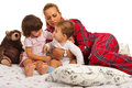 Mother with kids in bed looking at her little who embracing together Royalty Free Stock Photography