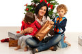 Mother with kids at christmas and her sitting near tree in their home Stock Photography