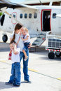 Mother and kids in front of airplane Stock Image