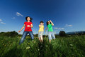 Mother with kids jumping active family running on green meadow Stock Photo