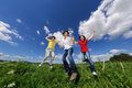 Mother with kids jumping active family running on green meadow Stock Images