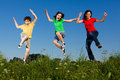 Mother with kids jumping active family running on green meadow Royalty Free Stock Images