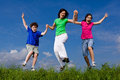 Mother with kids jumping active family running on green meadow Stock Photos