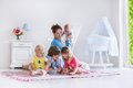 Mother and kids playing in bedroom children play indoors family with a white mom with baby boy girl reading books at home Royalty Free Stock Photography
