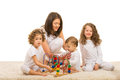 Mother and kids playing home her three with wooden toy Royalty Free Stock Photo
