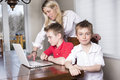 Mother with kids playing on laptop computer Royalty Free Stock Photo