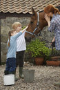 Mother and kids stroking horse outside stable side view of children Stock Photography