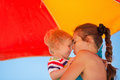 Mother kissing baby on beach under umbrella Royalty Free Stock Photo