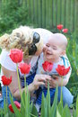 Mother kissing baby boy in garden of tulips Royalty Free Stock Photo