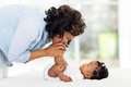 Mother kissing baby feet happy african american while playing on bed Royalty Free Stock Images