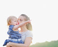 Mother kissing baby pointing on copy space Royalty Free Stock Photos