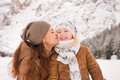 Mother kissing child outdoors among snow-capped mountains Royalty Free Stock Photo