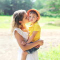Mother kissing child outdoors in sunny summer