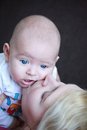 Mother kissing her angelic baby boy baby spitting up closeup portrait Stock Images
