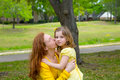 Mother kissing her blond daughter in green park outdoor dressed yellow Stock Images