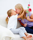 Mother kissing her daughter Stock Images
