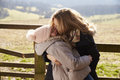 Mother kissing her daughter by a gate in the countryside Royalty Free Stock Photo
