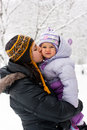 Mother kissing her daughter in winter Royalty Free Stock Image