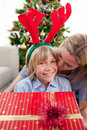 Mother kissing her son at Christmas time Stock Photography
