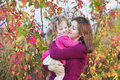 Mother kissing her toddler daughter in garden Royalty Free Stock Photo