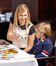 Mother letting child tasting broccoli in a restaurant Stock Photography