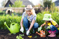 Mother and little daughter planting vegetable in