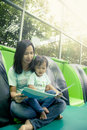 Mother and little daughter reading book together in library Royalty Free Stock Photo