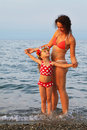 Mother and little daughter standing on beach Stock Photography