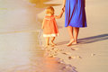 Mother and little daughter walking on beach Royalty Free Stock Photo