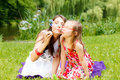 Mother and little girl blowing soap bubbles in park. Royalty Free Stock Photo