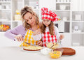 Mother little girl making cake together spreading filling Royalty Free Stock Images