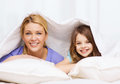 Mother and little girl under blanket at home family child concept smiling Royalty Free Stock Image
