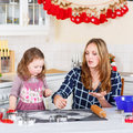 Mother and little kid girl baking gingerbread cookies for Christ Royalty Free Stock Photo