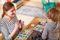 Mother and little son playing together education card game for c children Stock Photography