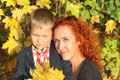 Mother and little son with yellow maples in autumn park at sunny day Royalty Free Stock Images