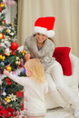 Mother looking on baby decorating Christmas tree Stock Image