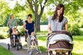 Mother looking at baby in stroller at park young with friends and children background Stock Image