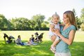 Mother looking at cute daughter in park happy with friends and children background Royalty Free Stock Image