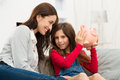 Mother looking at daughter holding piggybank smiling her sitting on couch Royalty Free Stock Photography