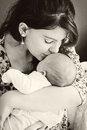 Mother loving her baby a young kissing newborn bw Royalty Free Stock Images