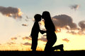 Mother lovingly kissing little child at sunset silhouette of a young her on the forehead outside in front of a in the sky Royalty Free Stock Photos