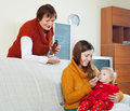 Mother with mature woman giving medicament to unwell baby young women girl at home Royalty Free Stock Photo