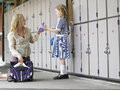 Mother packing daughter s school bag happy near lockers Royalty Free Stock Image